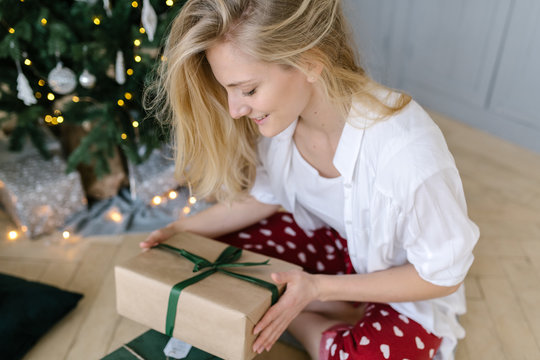 Woman with gift at Christmas tree