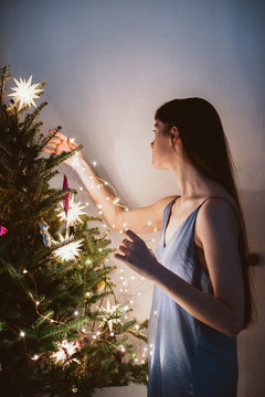 Woman decorates christmas tree at home