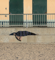Homeless person sleeping outside at the beach
