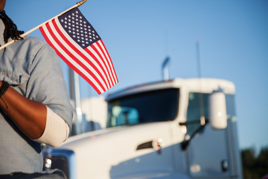 Truck driver holding an American flag.