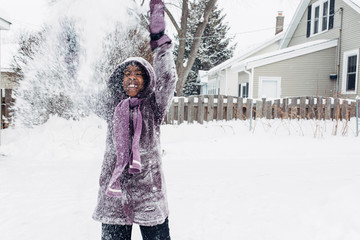 Black girl throwing fresh snow in the air