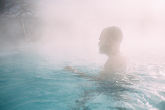 Young man swimming in a pool during cold winter days