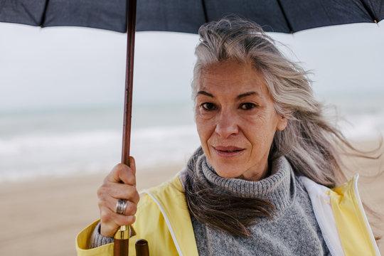 Senior woman holding an umbrella in a rainy day on the beach.