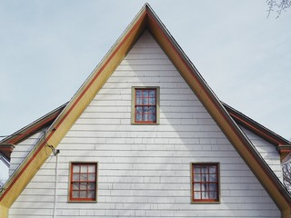 peak of a pointy old house with white siding and three windows that look like a face