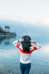 Back view of a young woman wearing hat and looking swiss alps