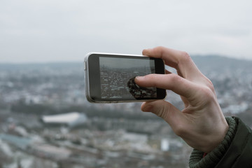 Young man takes pictures of the city from above with his phone