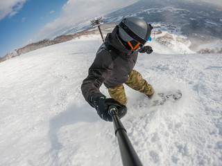 A snowboarder with action cam taking selfie on a ski slope at the Niseko