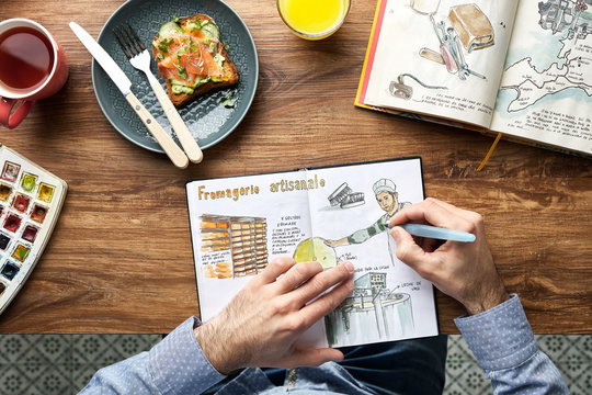 Man drawing in his notebook while having lunch at the cafe.