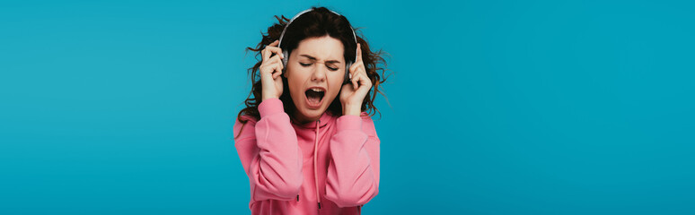 panoramic shot of attractive curly woman singing while listening music in headphones on blue Fotobehang
