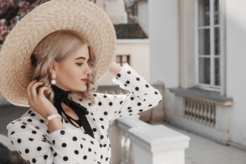 Outdoor fashion portrait of young beautiful lady wearing  trendy pearl earrings, stylish straw wide brim hat with ribbon tie, polka dot blouse, white wrist watch, posing in street. Copy, empty space