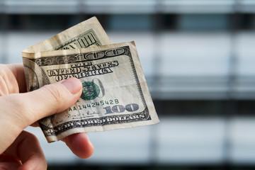hundred dollar bill in hand