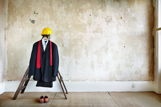 Suit, tie, shoes hard hat in an bare room