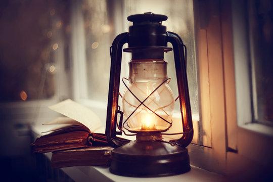 Kerosene lamp and old books