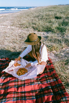 Brunette woman eating fish and chips at beach