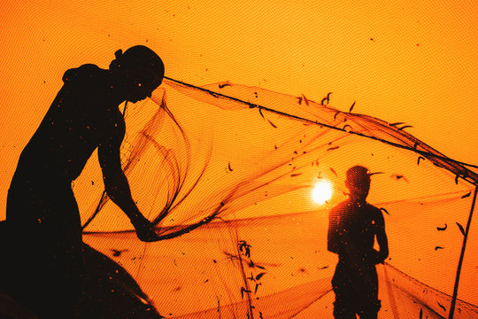 Anonymous, unrecognizable, silhouetted fisherman on the beach shore using fishing net during beautiful, golden sunset