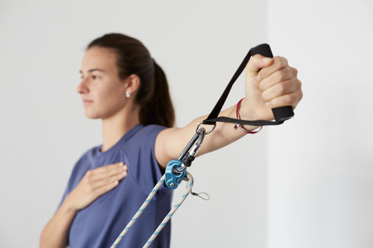 Young woman exercising with elastic rubber in a fitness center or at home