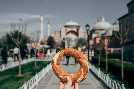 Woman holding pretzel in front of the Sultan Ahmet Mosque in Istanbul