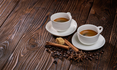Two cups of freshly brewed espresso coffee with coffee beans on a rustic wooden table