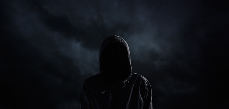 Spooky hooded person with obscured face