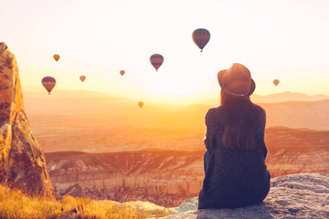 A woman alone unplugged sits on top of a mountain and admires the flight of hot air balloons in Cappadocia in Turkey. Digital detox and soul search Wall mural