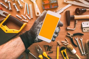 Handyman smartphone app, repairman holding mobile phone in hand