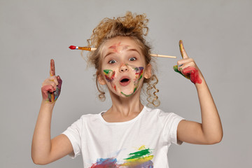 Beautiful little girl with a painted fingers is posing on a gray background. Fotoväggar