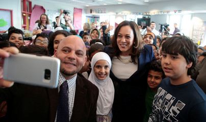 U.S. Senator Kamala Harris and school principal Radewin Awada take a selfie photograph with students at Miller Elementary School in Dearborn,