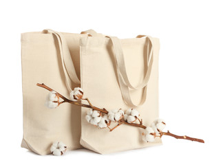 Stylish eco bags and cotton flowers on white background