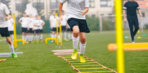 Boy Soccer Player In Training. Young Soccer Players at Practice Session. Boys Running Youth Agility Ladder Drills. Soccer Ladder Exercises