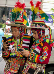 Two boys in traditional Bolivian dress look at their smart phones in Washington