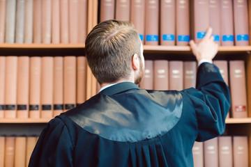 Anwalt mit Robe ist fertig für das Gericht, nimmt aber ein paar Bücher mit