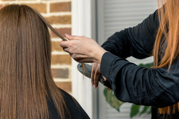Hairdresser cuts out a girl with long brown hair