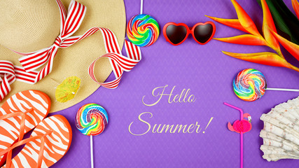 Summer vacation theme flatlay overhead with sunhat, lollipops, ice creams and sunglasses on purple background, with text gretting.