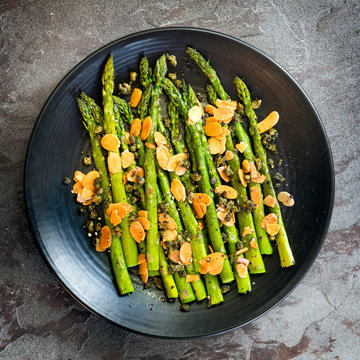 Roasted Asparagus with Toasted Almonds and Capers Top View on Slate