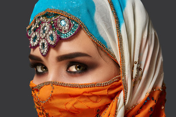 Studio shot of a chrming female wearing the colorful hijab decorated with sequins and jewelry. Arabic style.