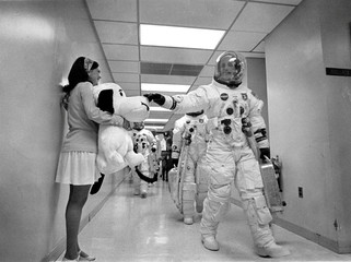 Mission commander Thomas P. Stafford pats the nose of Snoopy as the Apollo 10 crew walks along a corridor on the way to Launch Complex 39B