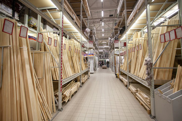 Sale in DIY shopping center. Lumber warehouse with wooden planks. Professional retail market for carpenter and builder.