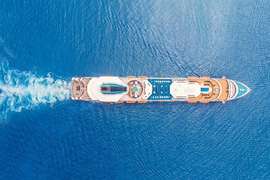 Cruise liner ship in ocean with blue water. Aerial top view