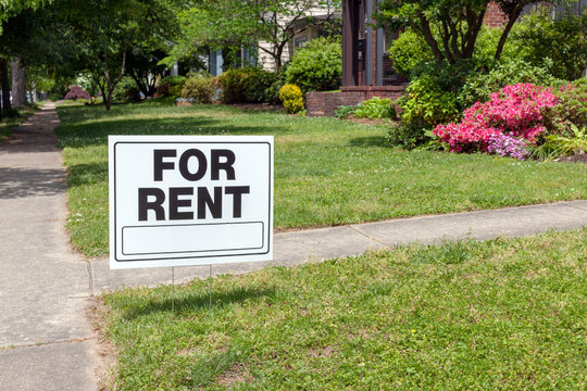 FOR RENT sign posted in lawn advertising home for rent.