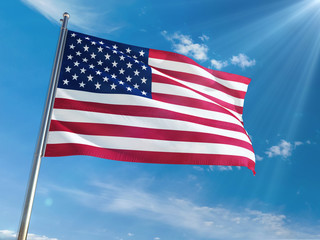 United States National Flag Waving on pole against sunny blue sky background. High Definition