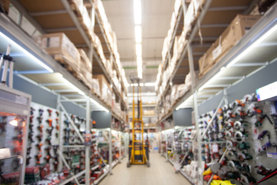 Close up blurred concept of working loader in stock. DIY megamall . Shopping center for professional builders, workers and electricians.