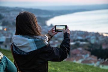 Girl taking photo in sinop sunset in turkey