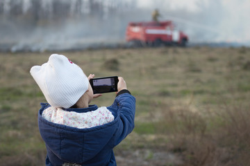 girl shoots video on the phone as a fire engine puts out a forest fire
