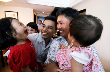 Reuters reporters Wa Lone and Kyaw Soe Oo celebrate with their children after being freed from prison, after receiving a presidential pardon in Yangon