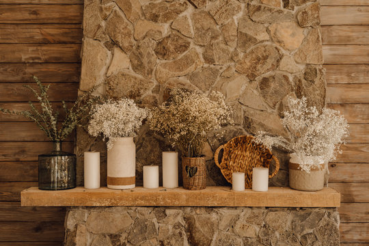 Fireplace Mantelpiece Decor Living Room Interior. Beautiful Country Brown Wooden Wall Copy Space. Rustic Vintage Stone Mantle with Candle and Flower