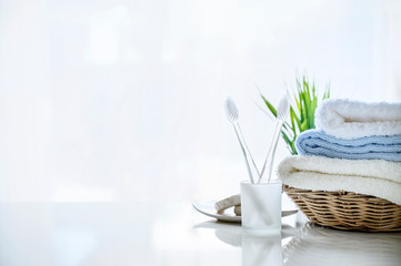 Mockup soft towels in basket and toothbrush on white background.