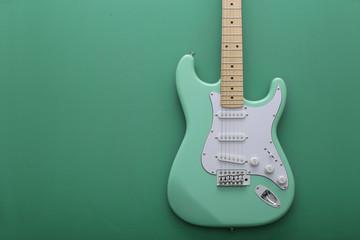 緑色の背景に置いたパステル緑色のエレキギターストラトキャスター