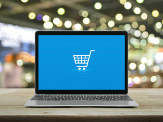 Shopping cart flat icon with modern laptop computer on wooden table over blur light and shadow of shopping mall, Business shop online concept