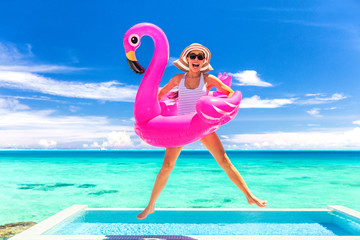 Summer vacation fun funny woman jumping with flamingo swimming pool float around waist excited of tropical hotel holiday. Wall mural