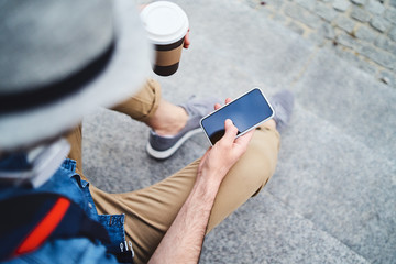 Close up of man sitting on stairs outside using smartphone and having coffee